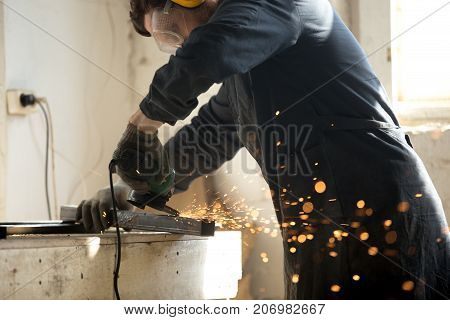 Close up of trained worker in protective workwear, gloves and glasses using angle grinder to smooth metal of profile pipe in workshop. Concentrated on metalwork skilled workman grinding steel parts