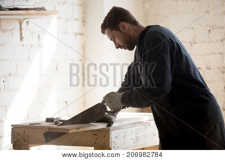 Enthusiast passionate about woodworking hobby cutting wooden board with old-fashioned hand saw on workbench at workshop. Restorer of antique furniture working at new project. Home based business idea