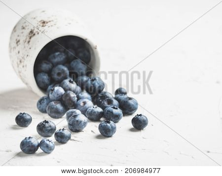 Blueberries on white concrete background. Blueberry border design. Fresh picked bilberries scattered close up. Copyspace. Closeup
