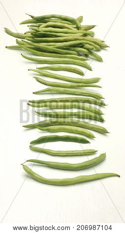 String bean raw food isolate on wood white sort spacing and macro photo.