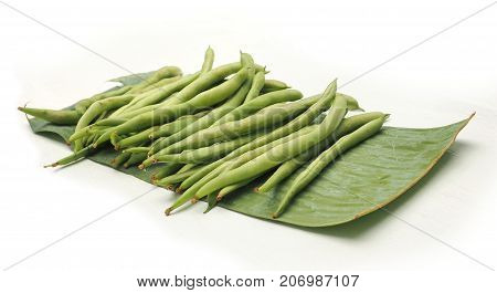 String bean raw food on banana leaf isolate on wood white has clipping paths and macro photo focus at center around are blur.