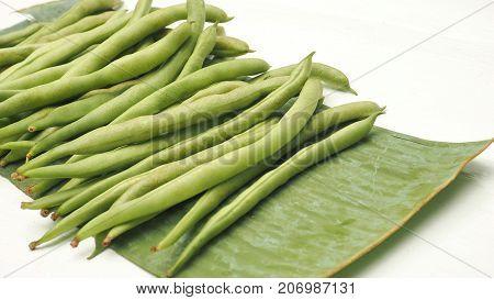 String bean raw vegetable on banana leaf isolate on white wood.