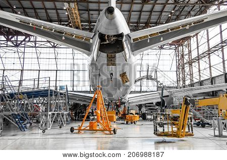 Large Passenger Aircraft On Service In An Aviation Hangar Rear View Of The Tail, On The Auxiliary Po