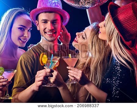 Cocktail party with group people dancing and drink cocktail. Women and men have fun in night club. Happy couple with alcohol drink on foreground and disco ball on background. Opening of new strip club