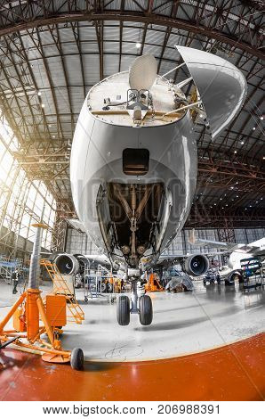 A Large Passenger Aircraft On The Service In The Aviation Hangar View The Nose And Radar Under The H