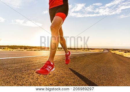 Running shoes on male triathlete runner - closeup of feet running on road. Man jogging outside exercising training for triathlon ironman outside at sunset.