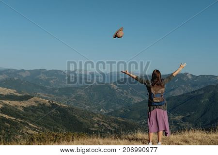 Young Woman Traveler Tosses A Hat Against The Background Of The Mountains.  Freedom Concept