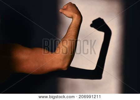 Physical strength and weakness. Strong hand of the sportsman and its reflection on the wall a thin shadow. Expected and reality. Sports achievements and victory