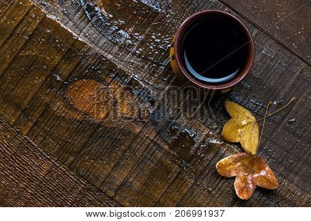Cup of  black coffee and  autumn leaves on  old  wet wooden table.  Flat lay