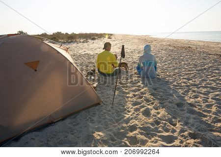 Couple Of Travelers Drinking Coffee Next To Tent