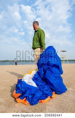 Friends Lay Out A Paraglider Before Training