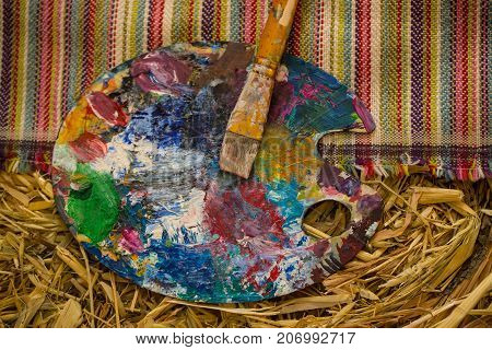 Paint brush palette icon art tools against background hay and straw. Multicolored palette for painting and creativity creative thinking artist workshop. Background for art. Bright oil-paint palette