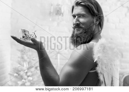 Black and white photo of muscular bearded man wearing wings acting like a Christmas angel.