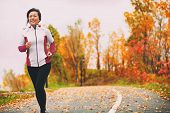 Mature Asian woman running active in her 50s. Middle aged female jogging outdoor living healthy lifestyle in beautiful autumn city park in colorful fall foliage. Asian Chinese adult in her fifties. poster