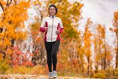 Middle aged mature Asian woman running healthy lifestyle Chinese lady jogging in fall park in her 50s. Middle age runner outdoor living in autumn city forest happy on weight loss fitness program. poster