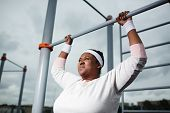 Persistant chubby girl trying to do difficult exercise while hanging on bar of outdoor sport facilities poster