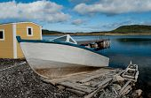 Boat on a Wooden Ramp:  A weathered fishing boat sits on a handmade ramp for launching into a bay on the west coast of Newfoundland. poster
