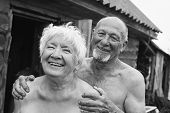 Authentic black and white portrait of funny ridiculous old couple of bearded bold man and charming woman with grey hair and lovely smile. Two grannies are laughing outdoor of bathhouse. Village life. poster
