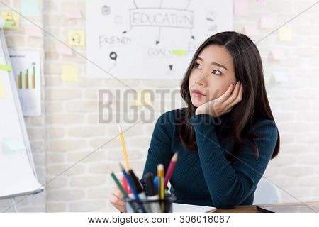 Young Asian Female Oversea College Student Thinking With Hand On Cheek At The Table In Class Room