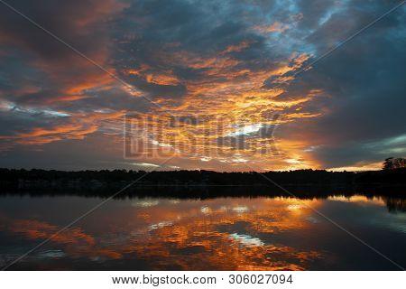 A Striking Nature Orange Coloured Stratocumulus Cloudy Coastal Sunrise Seascape Over Sea Water With