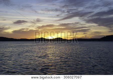 A Striking Inspirational Gold Coloured Stratocumulus Cloudy Coastal Sunrise Seascape Over Sea Water