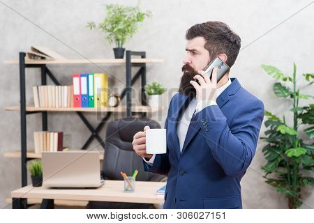 Man bearded businessman hold cup and smartphone. Mobile call. Start day with coffee. Coffee relaxing break. Boss enjoying energy drink. Coffee is pledge of successful negotiations. Caffeine addicted. poster