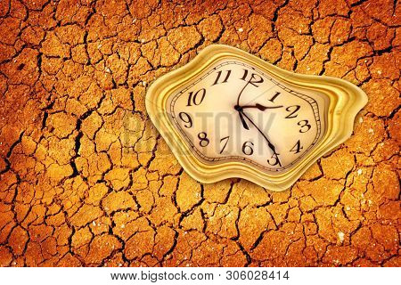 Conceptual image of close up clock face on dried and cracked landscape