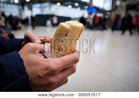 closeup of a caucasian man eating a sandwich in a train station or a tram station poster