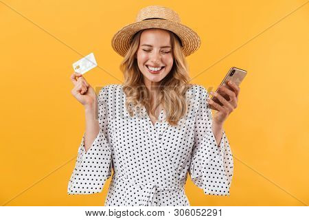 Beautiful young blonde woman wearing summer dress standing isolated over yellow background, showing plastic credit card while using mobile phone and celebrating