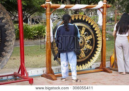 Thai woman people knock respect praying large nipple gong Phra That Nadoon Chedi or Wat Na Dun Pagoda at Mahasarakham city in Maha Sarakham, Thailand poster