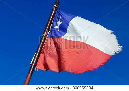 Broken National Flag Of Chile Flying With Blue Sky Background