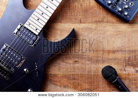 Body And Fretboard Of Modern Electric Guitar, Multi Effects Processor And Microphone On Rustic Woode