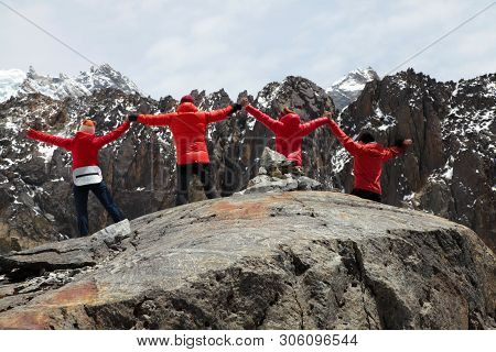 Active Hikeres In Red Jakets With The Raised Hands Enjoying The View. Himalayas. Nepal