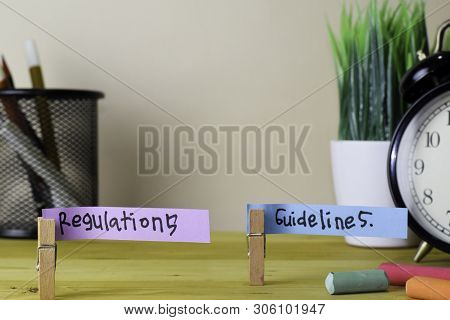 Regulations And Guidelines. Handwriting On Sticky Notes In Clothes Pegs On Wooden Office Desk
