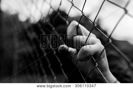 Young Unidentifiable Teenage Boy Holding The Wired Garden At The Correctional Institute In Black And