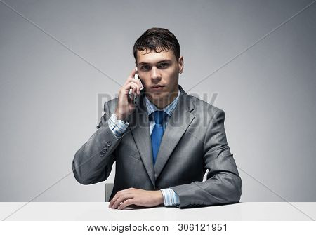 Young Man Talking On Phone And Looking At Camera. Businessman Sitting At Desk On Grey Wall Backgroun