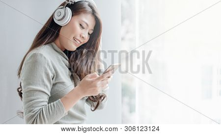 Beautiful Girl Is Working On Smartphone And Listening To Music By Headphone.office Girls Relax By Li