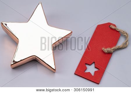 The Image Shows An Golden X-mas Star With Red Label, Isolated On Grey
