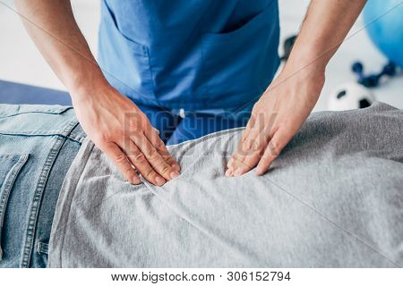 Cropped View Of Chiropractor Massaging Back Of Man In Hospital
