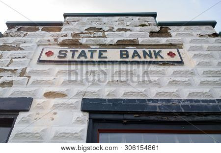 Original Architectural Facade, Paint Cracking And Blocks Peeling, Of An Old State Bank