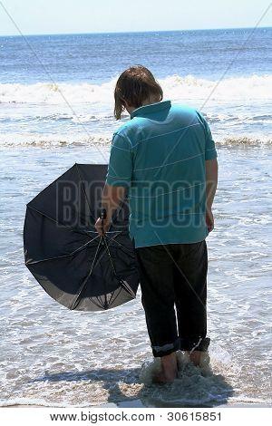 Teen With Umbrella Facing The Ocean