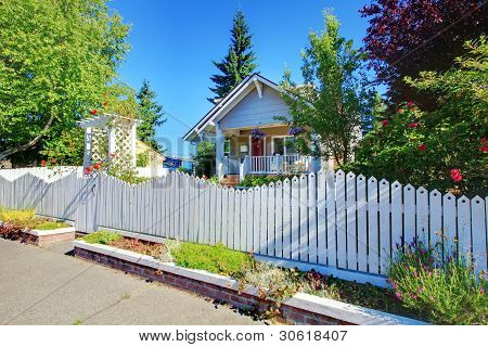 Cute Old Grey House Behind White Fence.