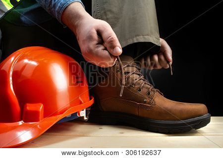 Photo of a worker lacing up leather boot on a surface with protective helmet.