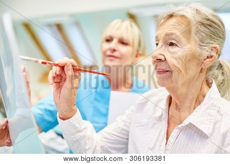 Senior woman with dementia while painting in creative painting class in a painting therapy
