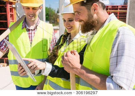 Low-angle view of a female architect or manager showing to her colleagues the electronic plan of the building on a tablet, during work on the construction site