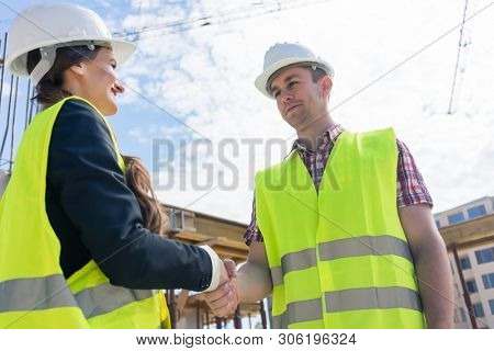 Low-angle view of a female architect and an engineer or supervisor smiling while shaking hands on the construction site of a new building poster