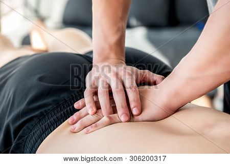 Therapist Giving Lower Back Sports Massage To Athlete Male Patient In Clinic