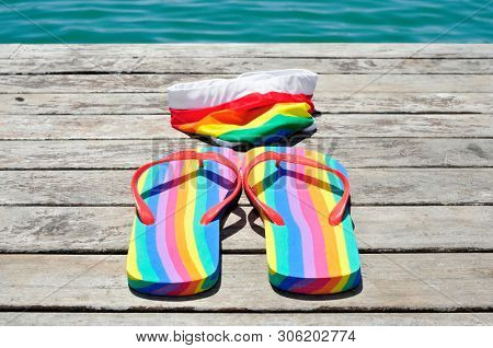 closeup of a pair of rainbow-patterned flip-flops and a rainbow-patterned swimsuit on a weathered dock, next to the ocean or a pond