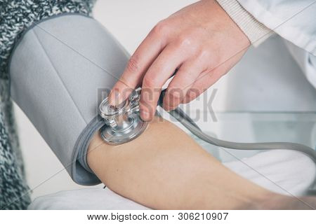 Doctor cardiologist measuring blood pressure of female patient in hospital office appointment