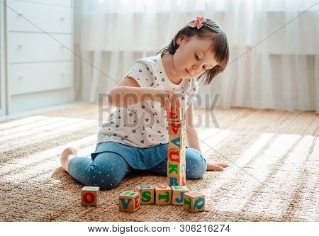 3 Year Old Child Plays With Wooden Cubes With Colorful Letters On The Floor In The Room A Little Gir